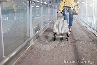 Asian woman traveler dragging  carry on luggage suitcase at airport corridor walking to departure gates