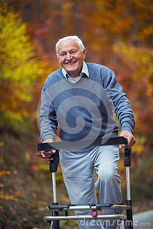 Senior man with a walking disability enjoying a walk in an autumn park