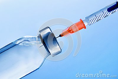 Vial with punctured syringe close up and blue background