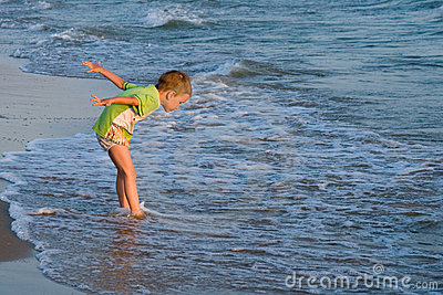Happy walking child on the sea