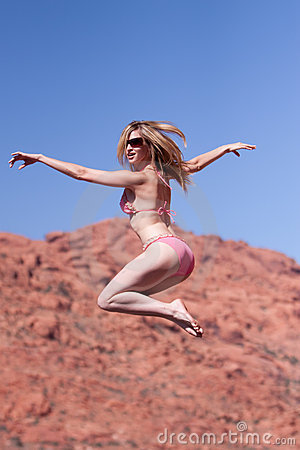 Woman in bikini jumping outdoors