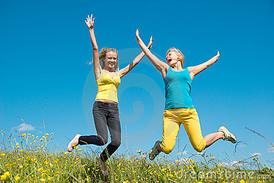 Young woman jumping on green meadow and blue sky