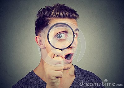 Curious young man looking through a magnifying glass