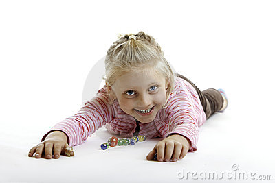 Happy Child is lying on the floor with marbles