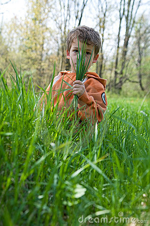 Boy hiding behind a fistful of grass