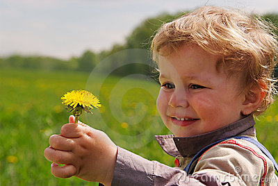 Adorable boy with dandelion in hand