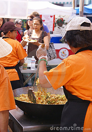 Asian cooks serving food at concessions.