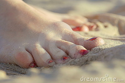 Women's feet wet in the sea sand