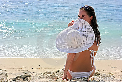 Brunette with white hat on beach