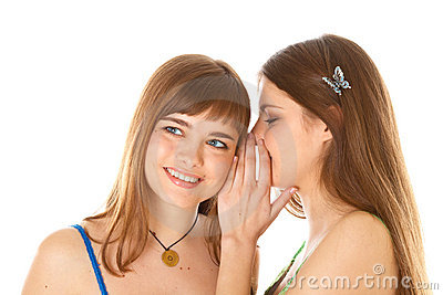 Two happy young girlfriends telling secrets