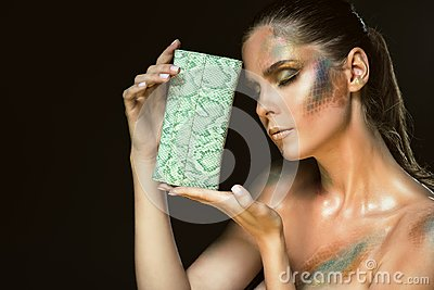 Close up portrait of gorgeous woman with closed eyes and artistic snakeskin make up holding green leather purse at her face