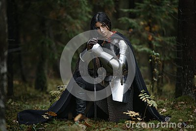 A beautiful warrior girl with a sword wearing chainmail and armor in a mysterious forest.