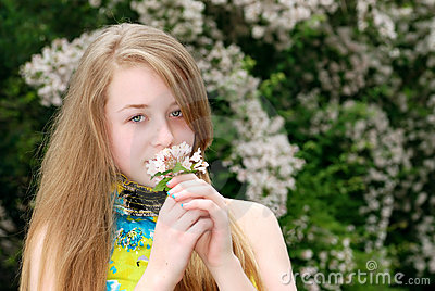 Young female teenager smelling flowers in a garden
