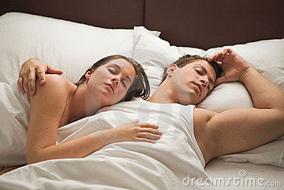 Young attractive couple sleeping in bed
