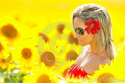 Beautiful young woman between sunflowers