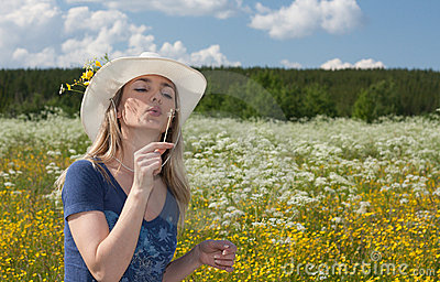 Beautiful girl blows on dandelion in white hat