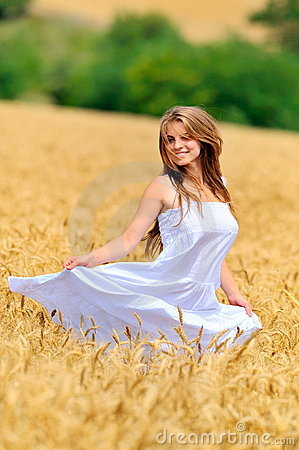 Young beautiful woman in golden wheat field