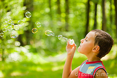 Cute kid blowing soap bubbles