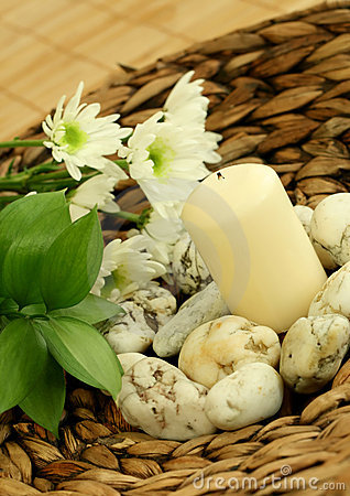 Spa concept. Candle, stones and flowers.