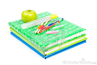 Stack of books with school suppley and green apple