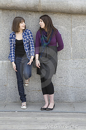 Two urban teen girls standing at wall