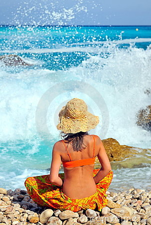 Young woman sitting by the sea