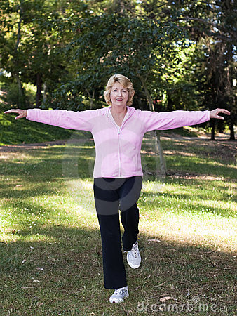 Senior woman balancing exercise in park