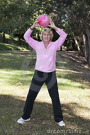 Senior woman throwing ball in park