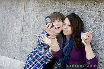Two urban teen girls taking photo by mobile phone