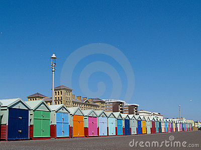 Beach huts lined up below clear blue sky.