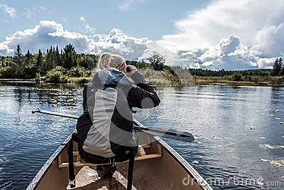 Girl using binocular on Canoe lake of two rivers in the algonquin national park in Ontario Canada on sunny cloudy day
