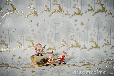 Christmas food photograph picture with iced mince pie and mini music playing santa claus on gold glitter reindeer wrapping paper