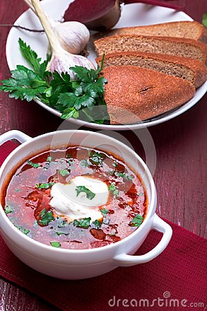 Ukrainian traditional borsch. Russian vegetarian red soup in white bowl on red wooden background. Borscht, borshch with beet.