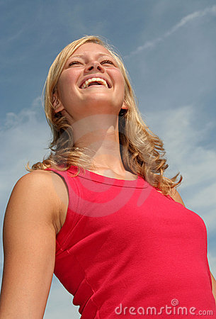 Woman laughing against blue sky