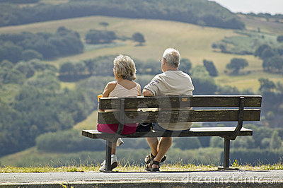 Two older people sitting on a bench