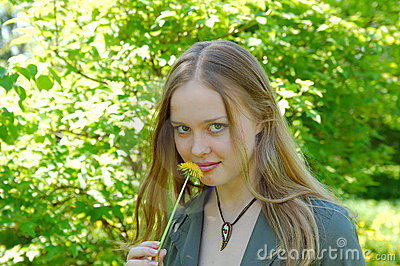Girl in park with mysterious smile and dandelion