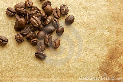 Grains of coffee on background of old book.