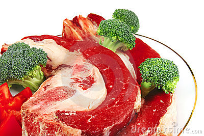 Uncooked steaks and vegetables