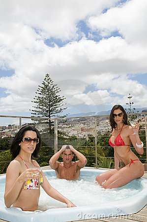 Two women and man relaxing in an outdoor jacuzzi