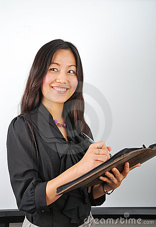 Smiling young Asian woman making notes