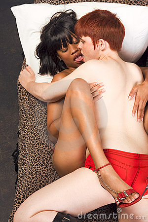 Young interracial lesbian couple in love kissing