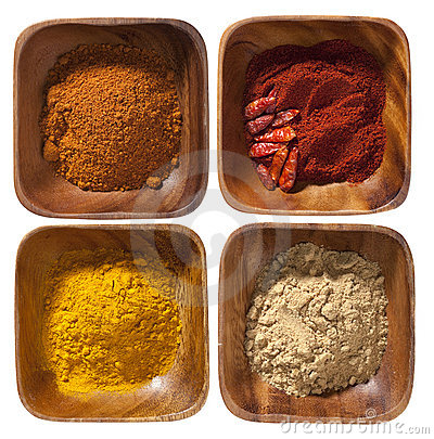 Four ground up spices in wooden bowels