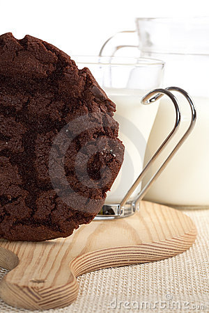 Chocolaty cookie and some milk on background