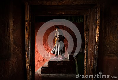 Tibetan monk woman goes down the stairs in Thiksey Monastery
