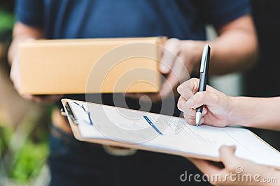 hand putting signature in clipboard to receive package from delivery man