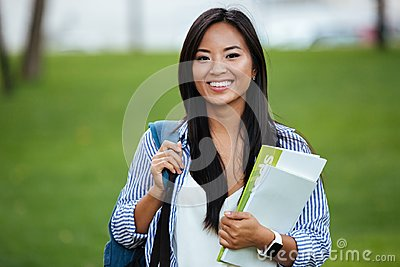 Young smiling asian student woman with backpack, holding noteboo