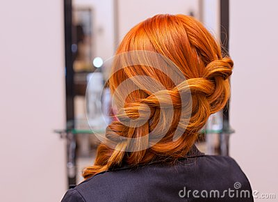 Beautiful girl with long red hair, braided with a French braid, in a beauty salon