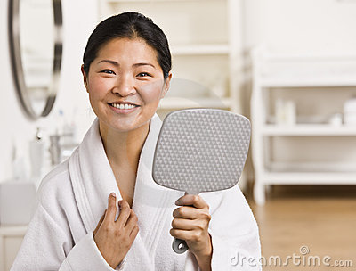 Asian woman holding mirror.