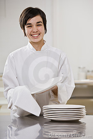 Smiling brunette drying dishes.
