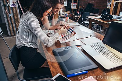 stock image of two female architects working together using color swatches sitting at desk with laptop, graphic tablet in design studio